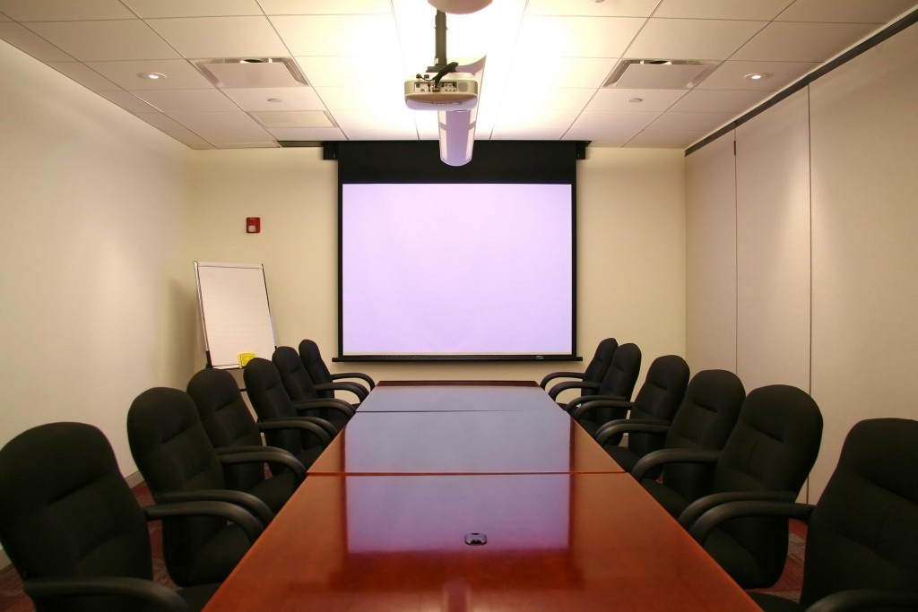 Meeting Room with White Screen Ready for a Presentation